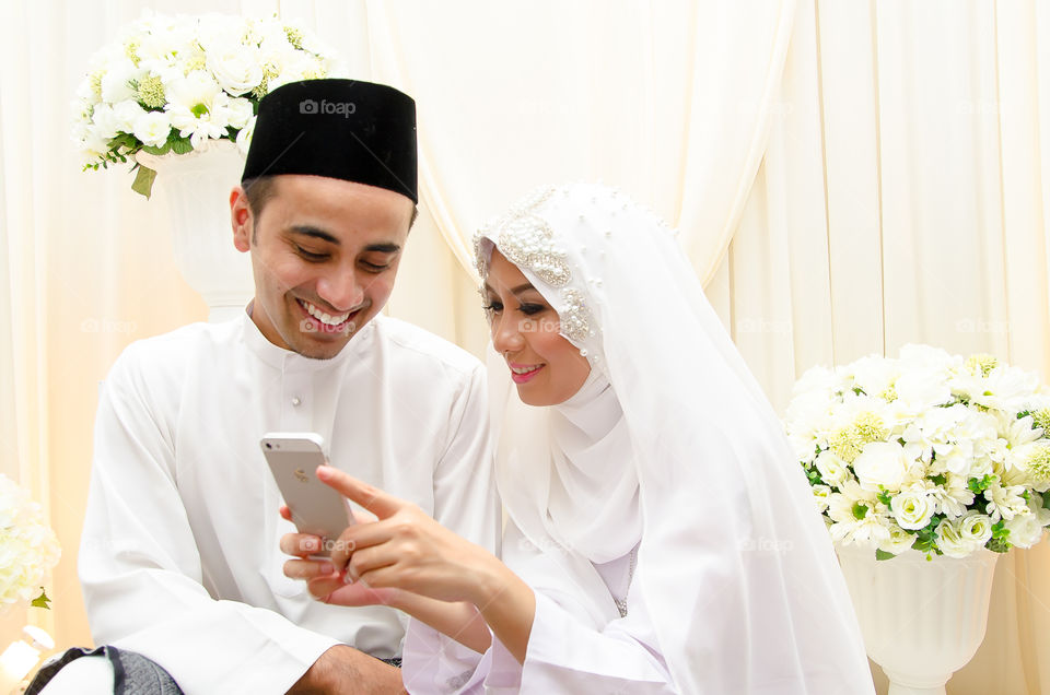Asian Muslim married couple using mobile phone