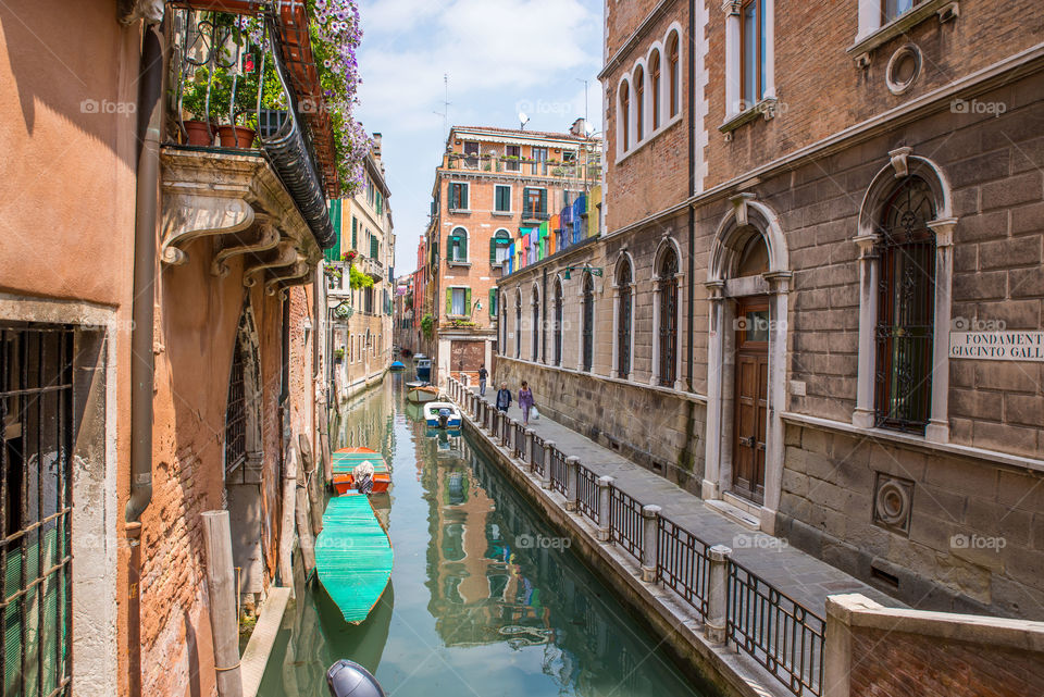 Boats moored in a small canal in venice