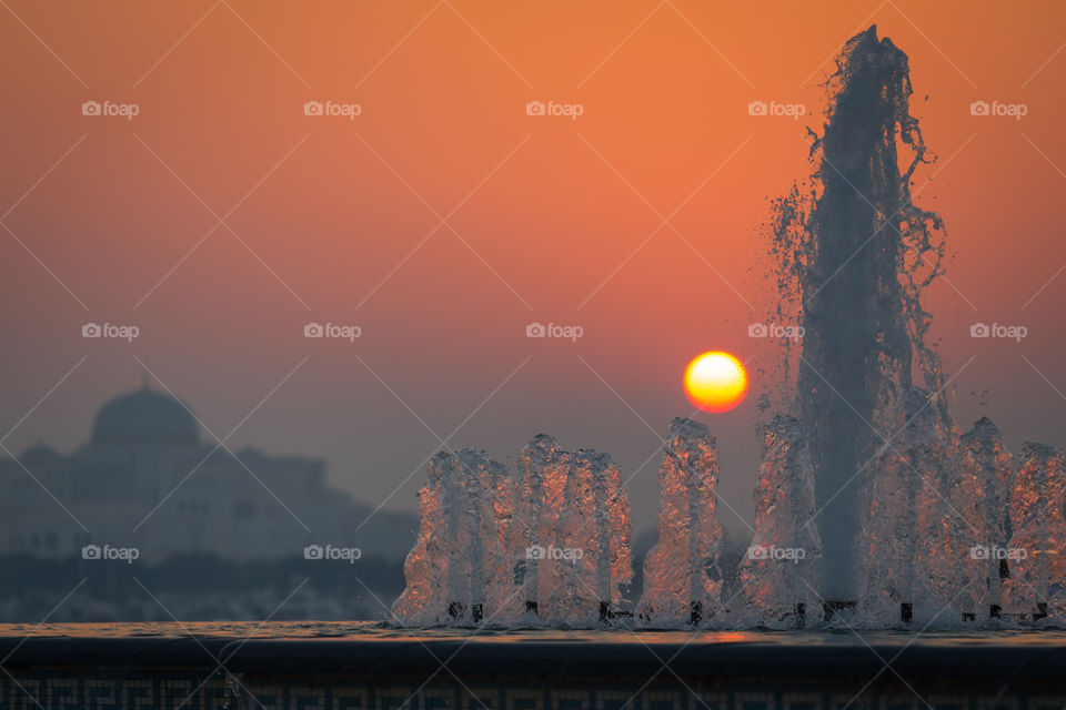 Summer sunset with refreshing fountain