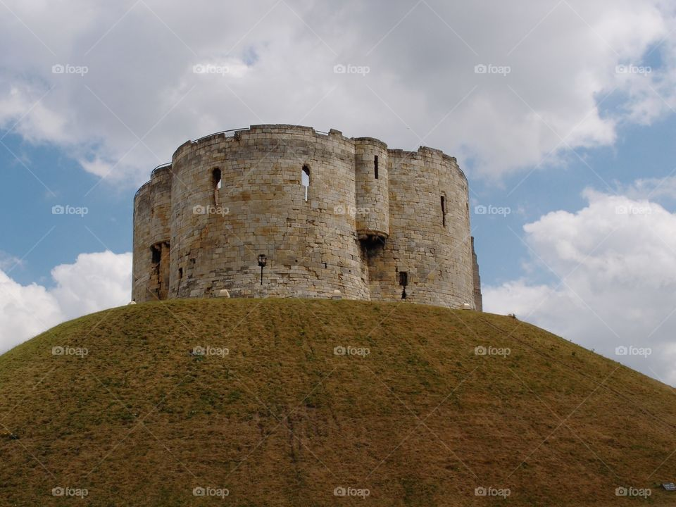 Clifford's Tower, a local stone landmark in York in England, sits majestically on top of a hill on a sunny day.