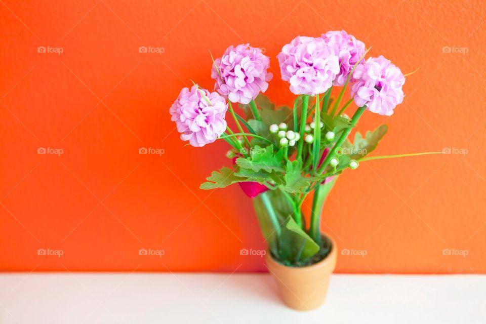 Cloth flowers on bright orange wall