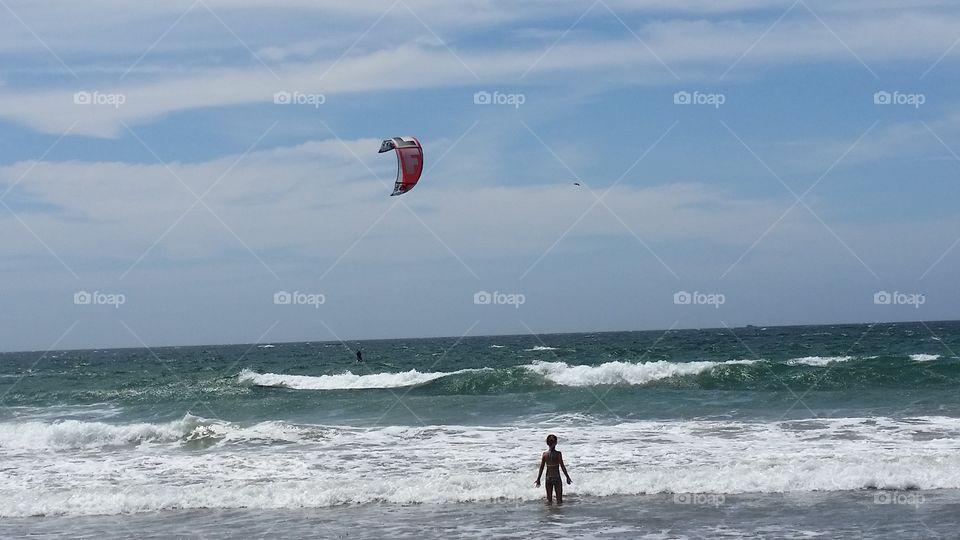 Kid watching a kite surfer in the ocean