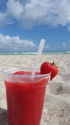 Glass of strawberry juice on beach