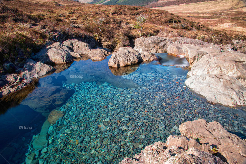 The rocky coastline and stones under the water