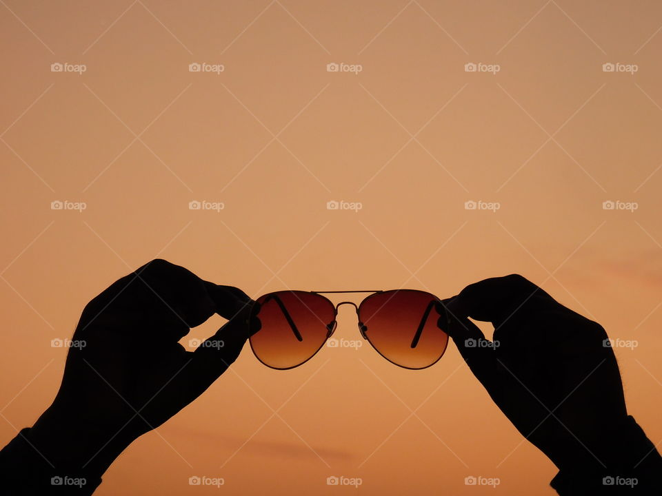 Silhouette image - sunglasses hold in hand with after sunset golden light background. it is creative image.