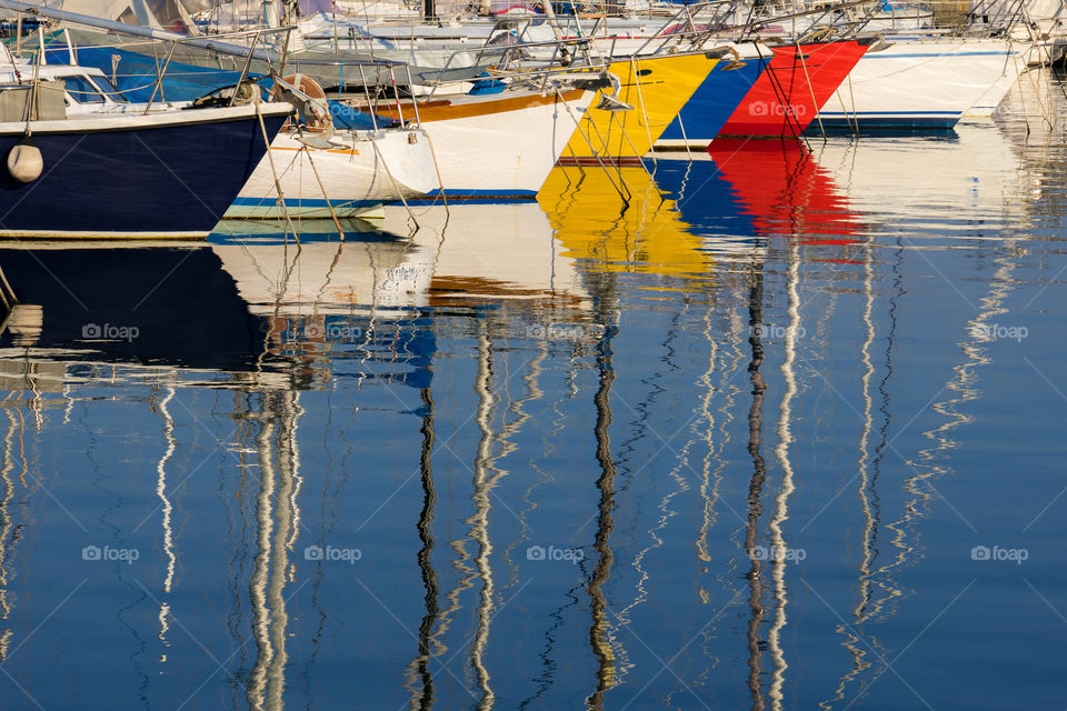 Reflection of multicolored boats in water