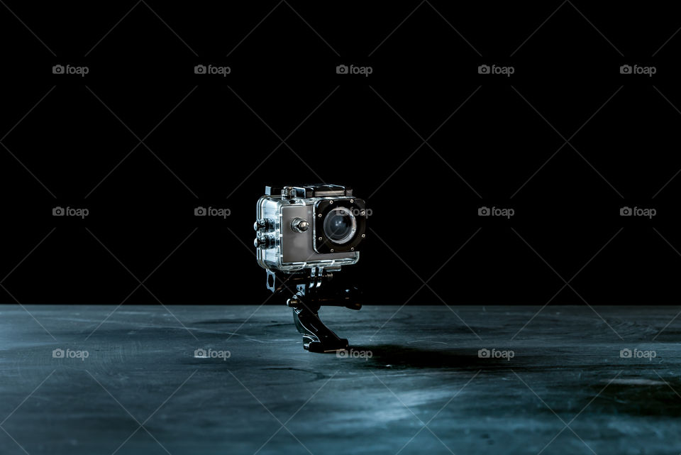 small action camera isolated on dark background as a symbol of photographic work