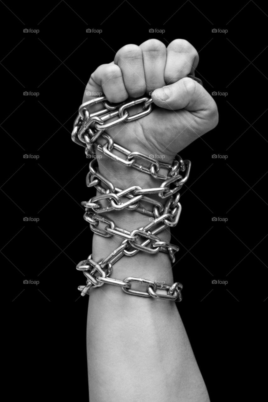 Fist of man in chains. Black and white