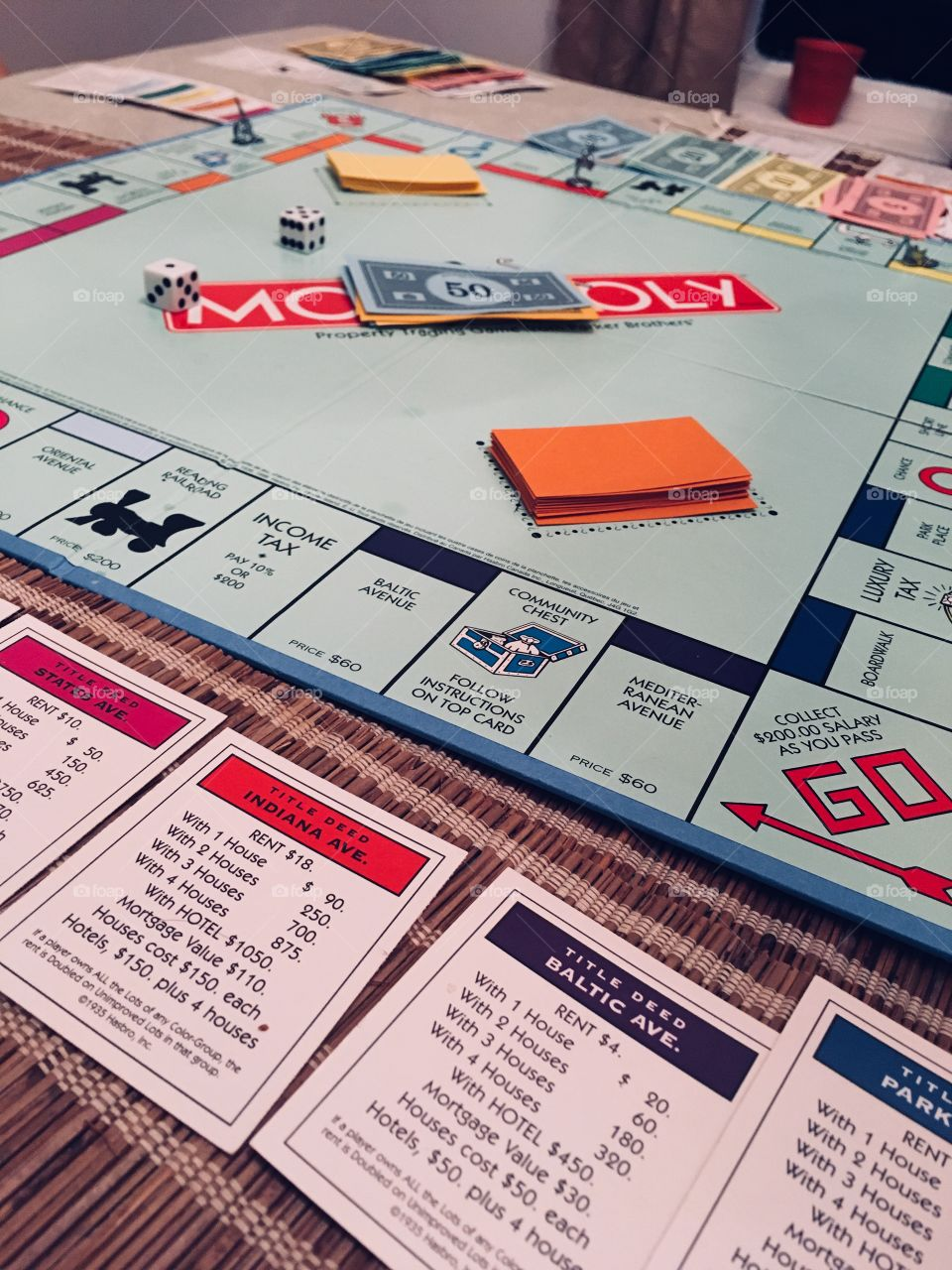 Monopoly board game in play. Dice, Monopoly money, chance cards, property cards laid out. Game night.