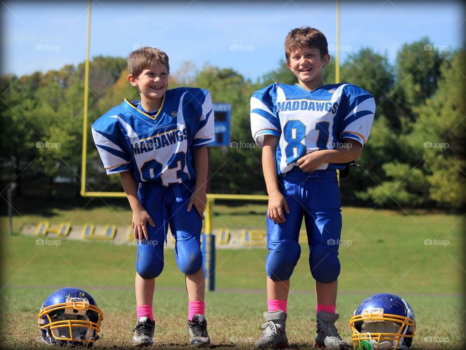 Football Brothers . Two handsome young brothers, suited up in their football uniforms.