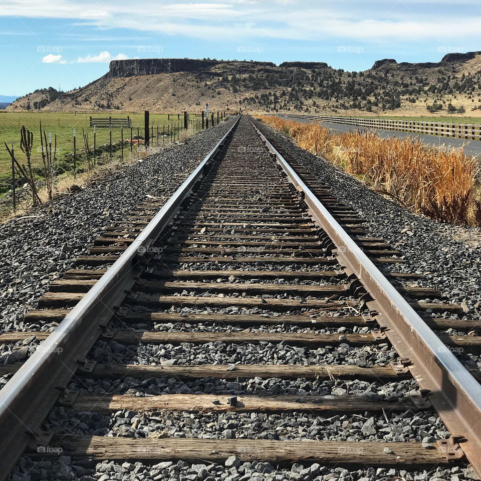 Symmetrical train tracks run up to the foot of a butte in rural Crook County in Central Oregon on a sunny day.