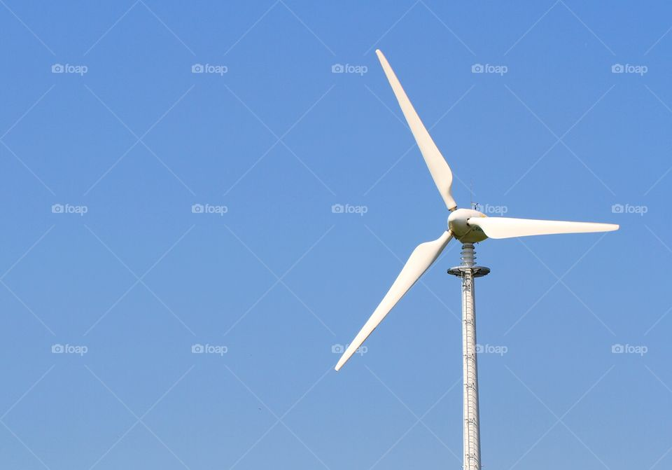 A wind turbine generating clean electricity through wind power with a bright blue sky behind.