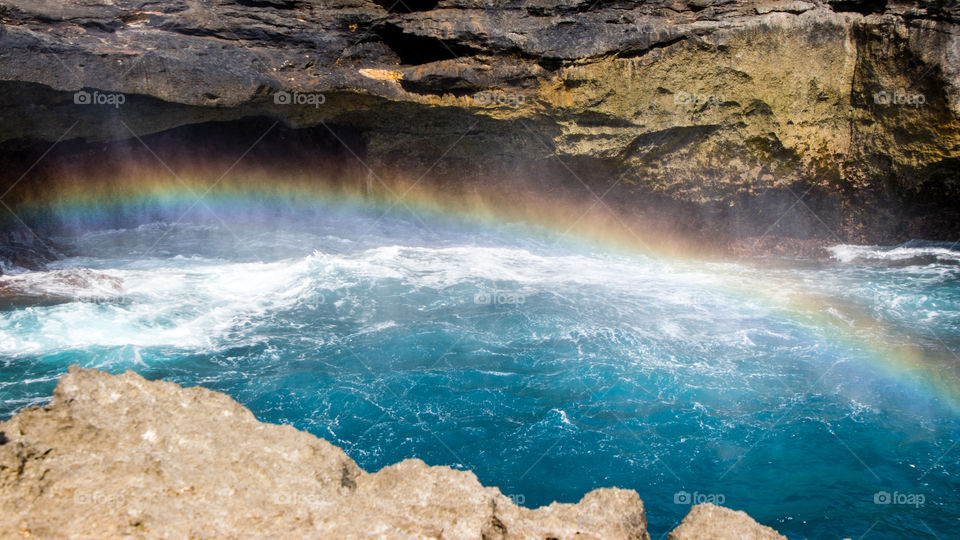Early morning rainbow over the cliffs of the Devil's Tear of Nusa Lembongan Indonesia