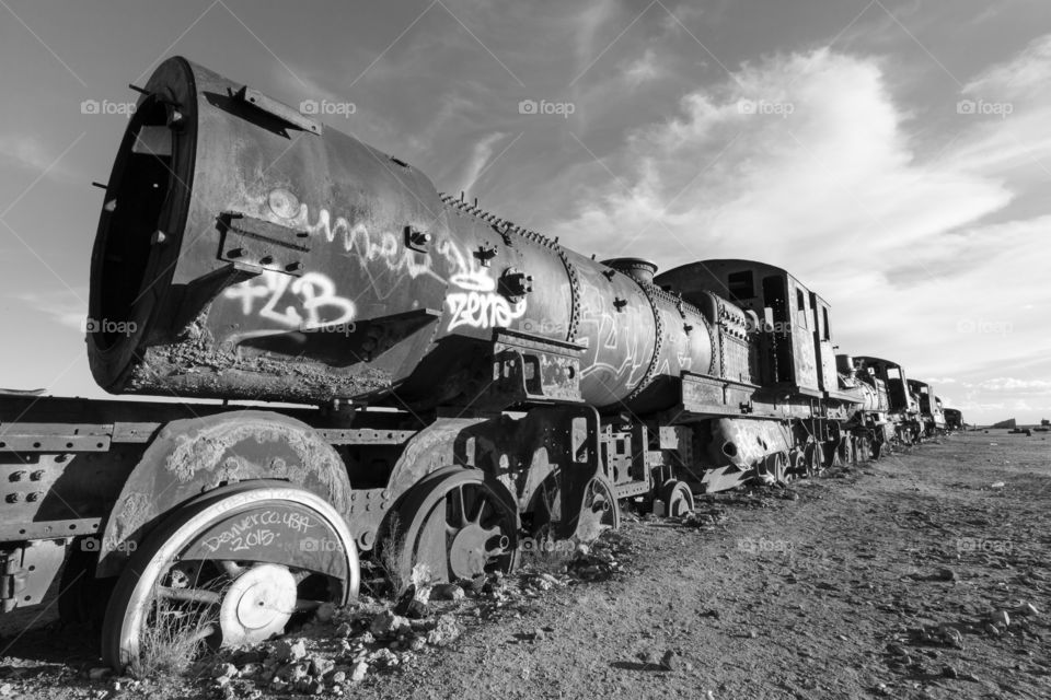 Abandoned train in desert. Abandoned old locomotive in desert. Black and white photo. Yuni, Bolivia. Train partly inside ground