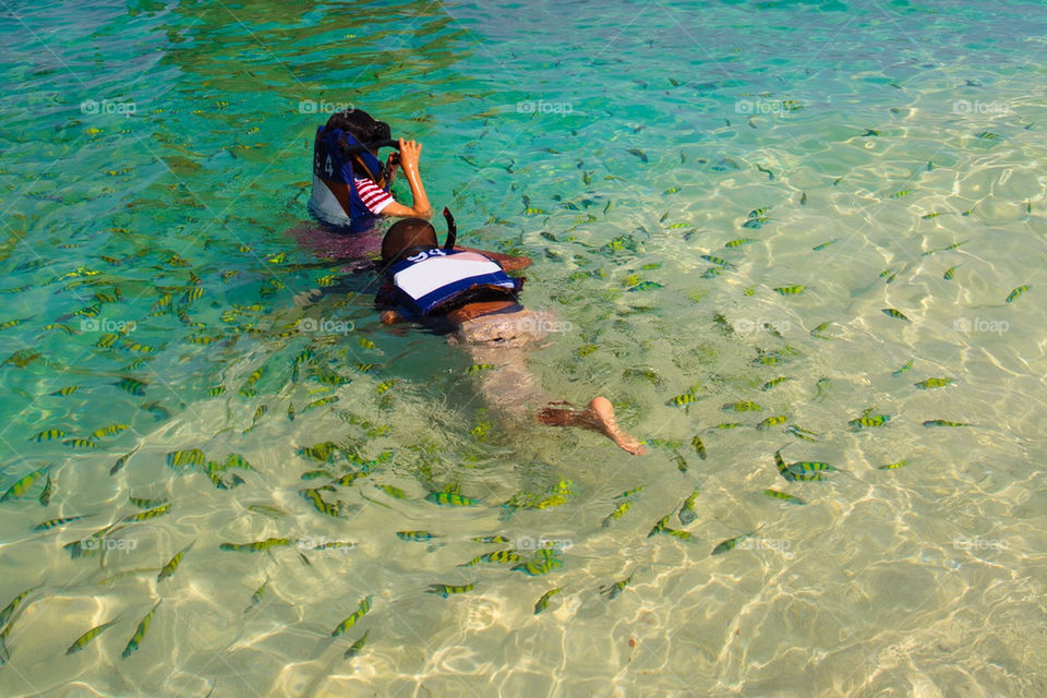 Kids snorkelling in tropical water with lots of fish