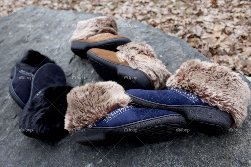 Three colorway slippers laying on side on rock