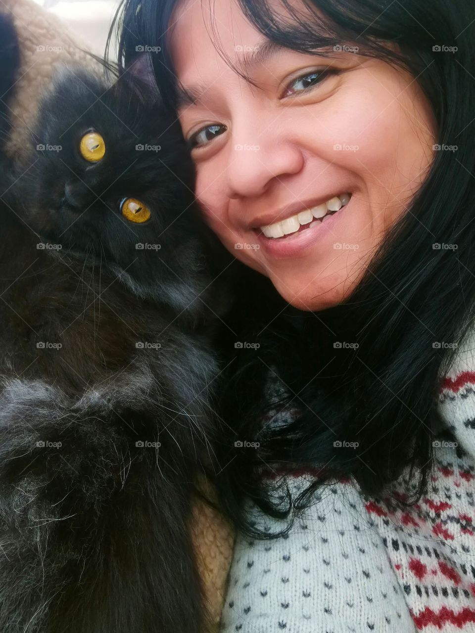 Lady selfie and is very happy with her cat. Friendship between human and cat. Concept of unconditional love and happiness.