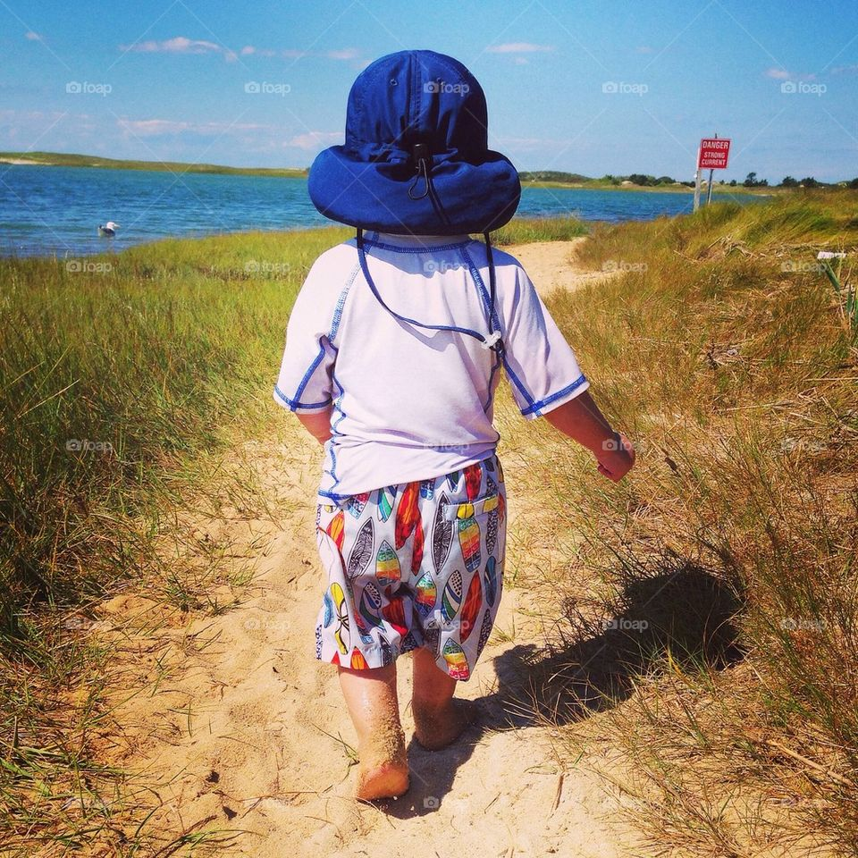 Rear view of a child walking at beach