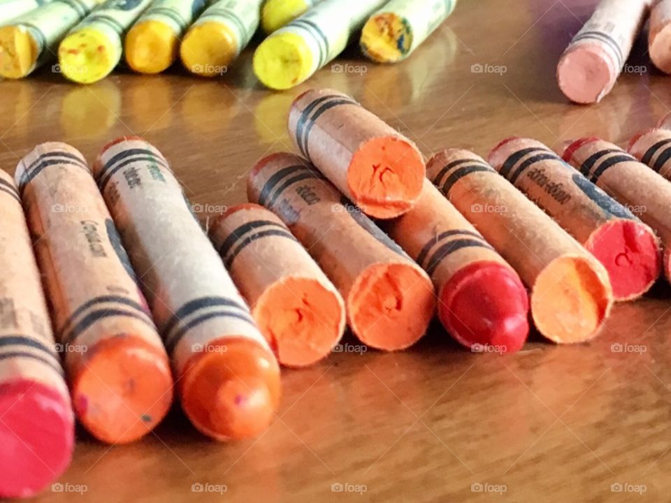 Orange, red and yellow crayons. Warm colours on wooden table.