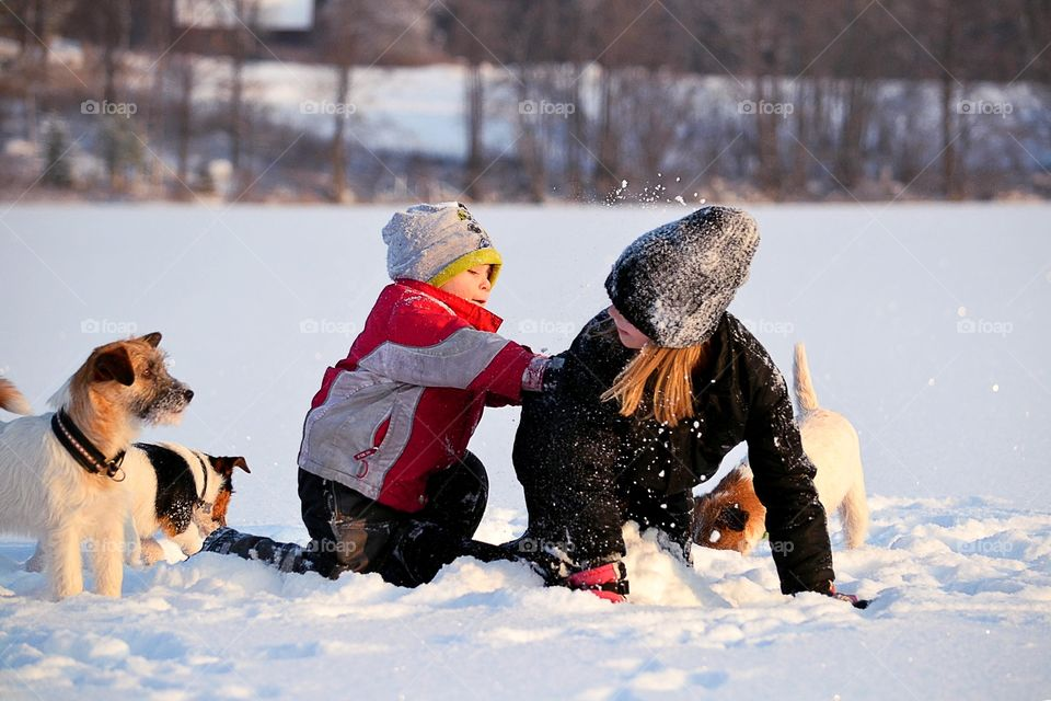 Brother playing with his sister in winter