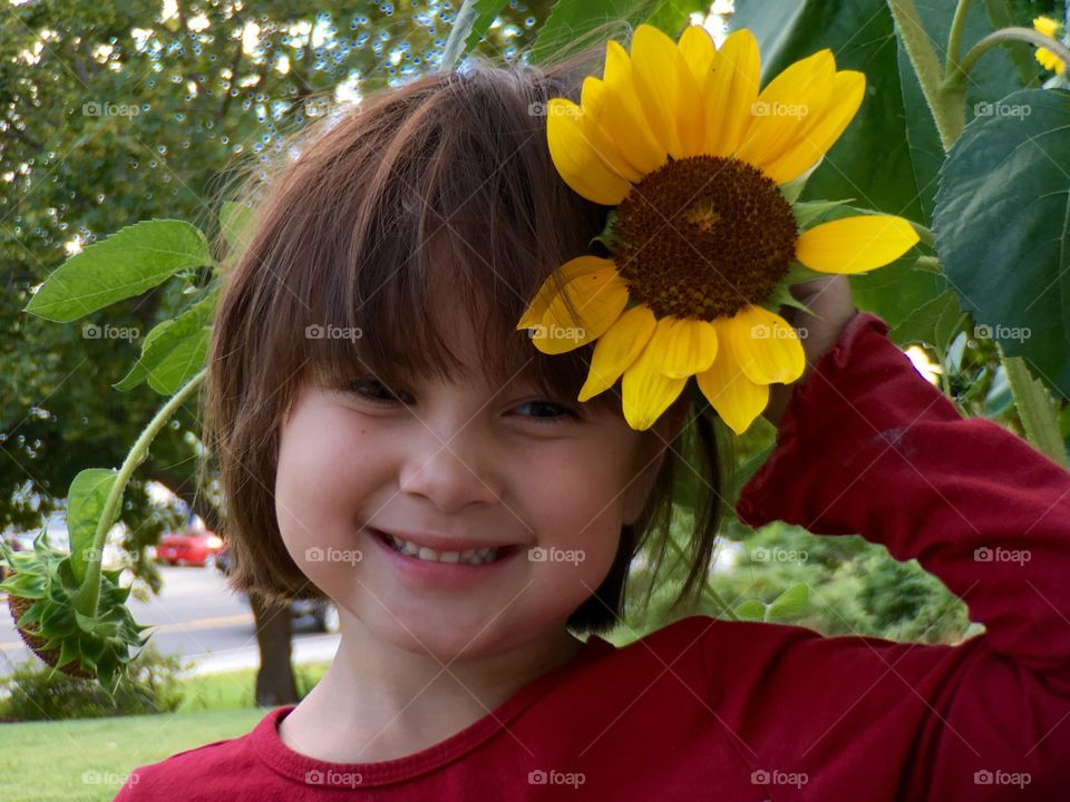 Cute girl holding yellow flower in hand