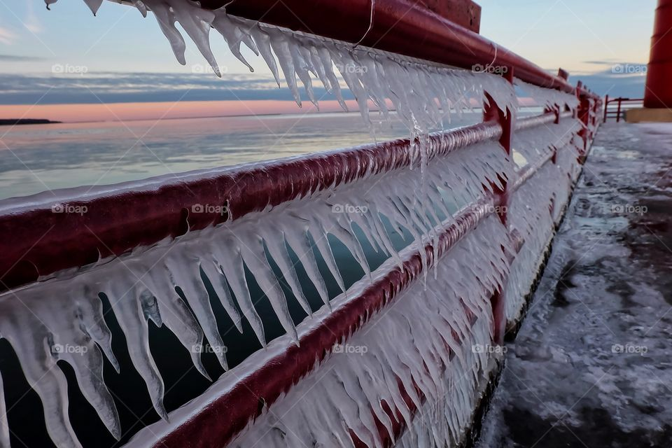 Icicles on red railing at sunset