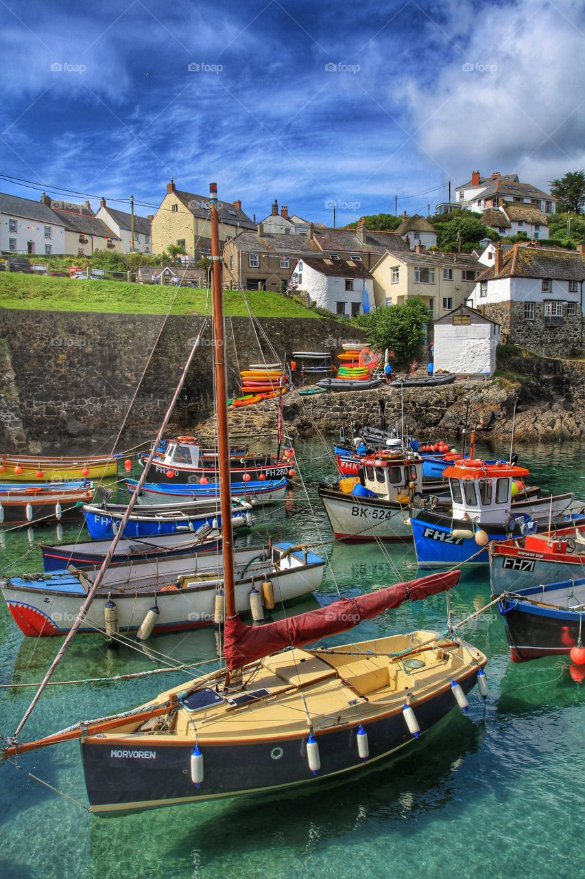 A busy Cornish harbour packed full of fishing boats and leisure craft on a beautiful sunny day.