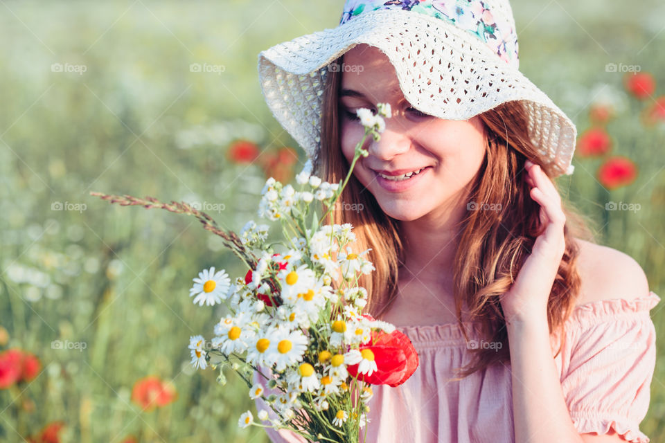 Beautieful young girl in the field of wild flowers. Teenage girl picking the spring flowers in the meadow, holding bouquet of flowers. She wearing hat and summer clothes. Spending time close to nature