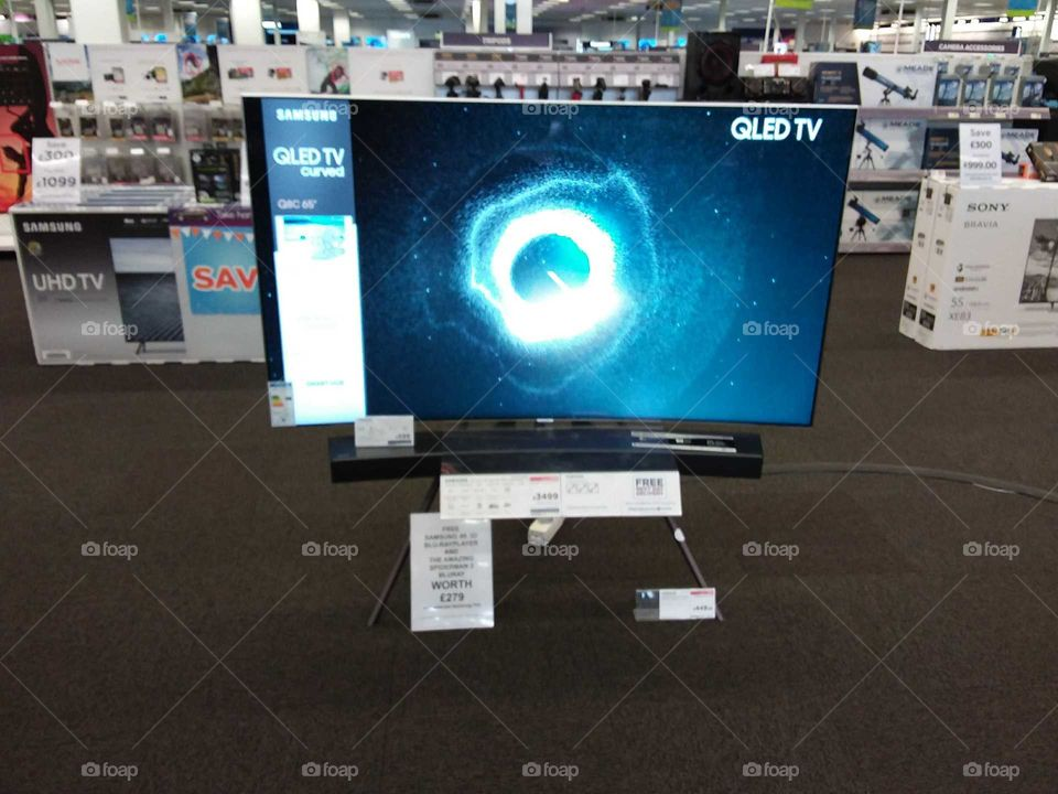 Samsung QLED television with soundbar mounted on studio stand 4K UHD TV