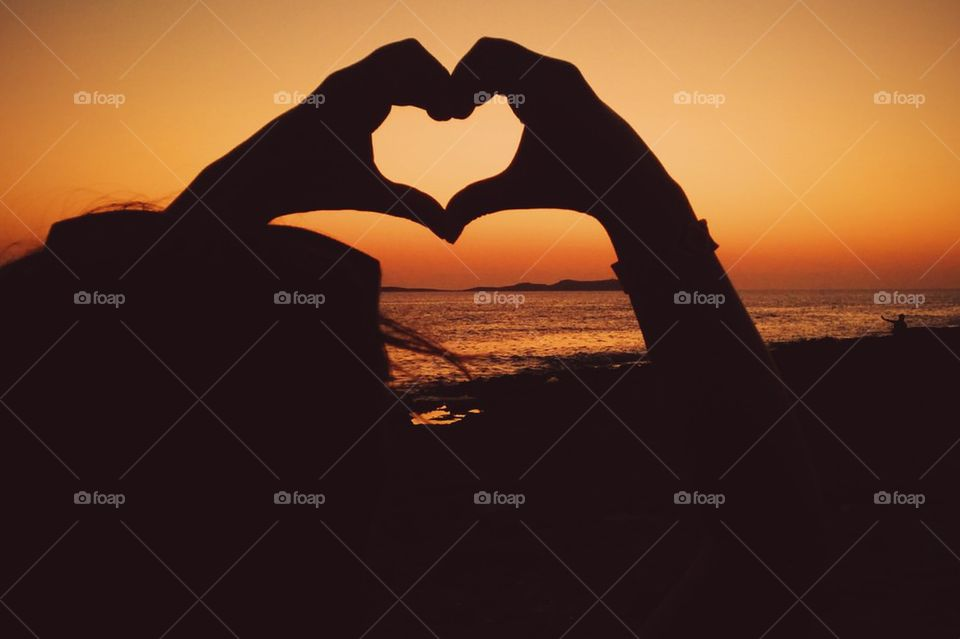 Silhouette of person making hearshape
