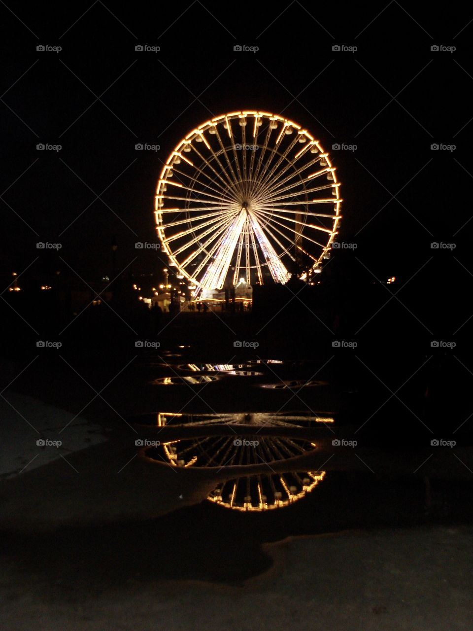 Reflection of Ferris wheel in puddles of water in the city of Paris, France at night.