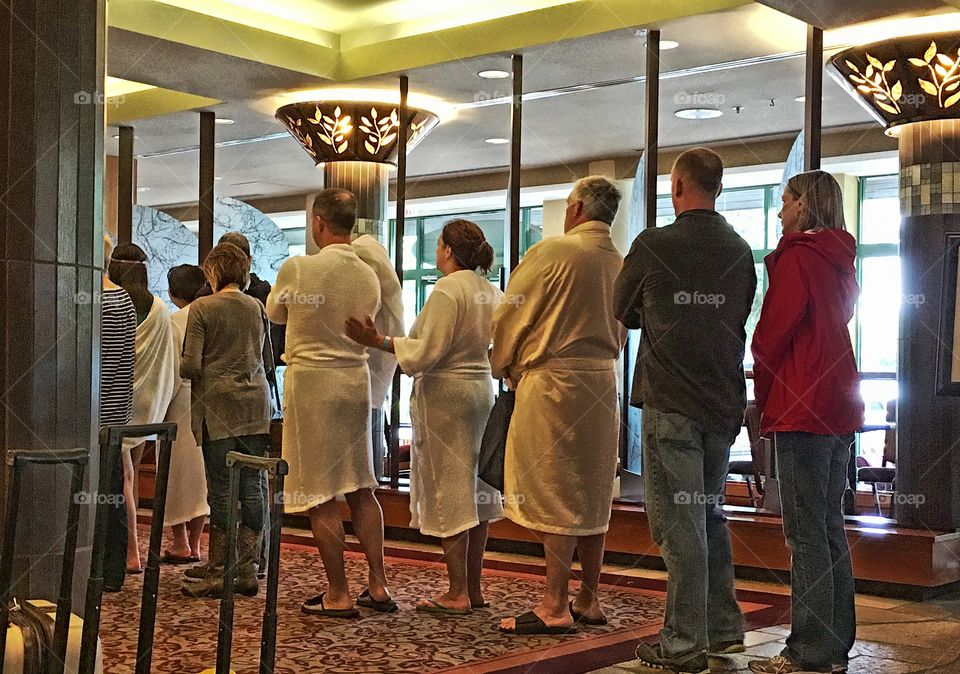 People in white spa bathrobes lined up in hotel lobby, Harrison hot springs resort