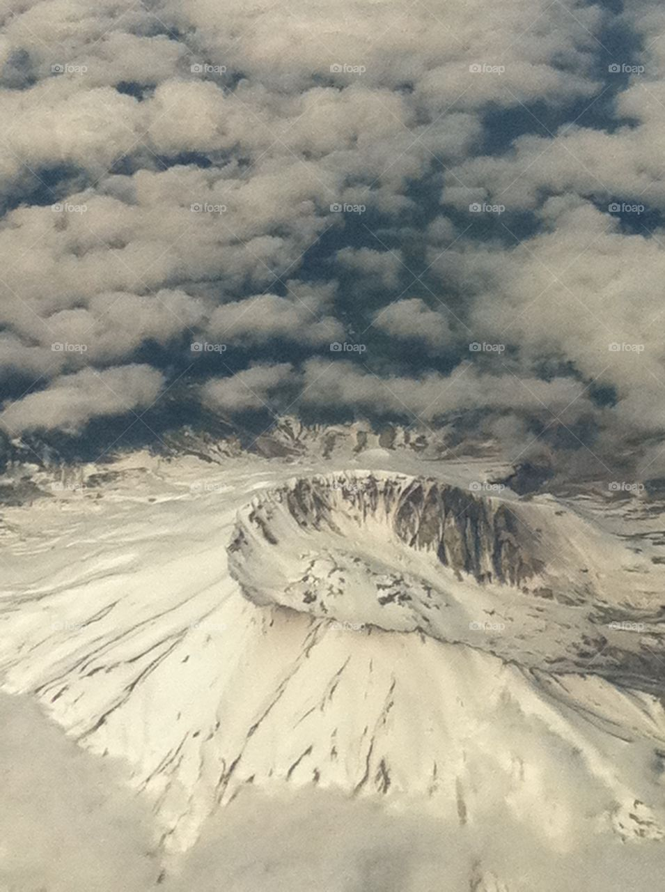 An arial view of Mount Saint Helens's dormant volcanic, snow covered crater. The view looking out from my window seat while on a flight to Vegas