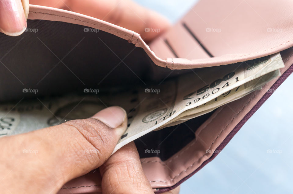 Businesswoman putting or taking out or paying Indian rupee banknotes from leather wallet. Isolated white background. Earning crisis growth bribe corruption bankrupt concept. Selective focus Close-up