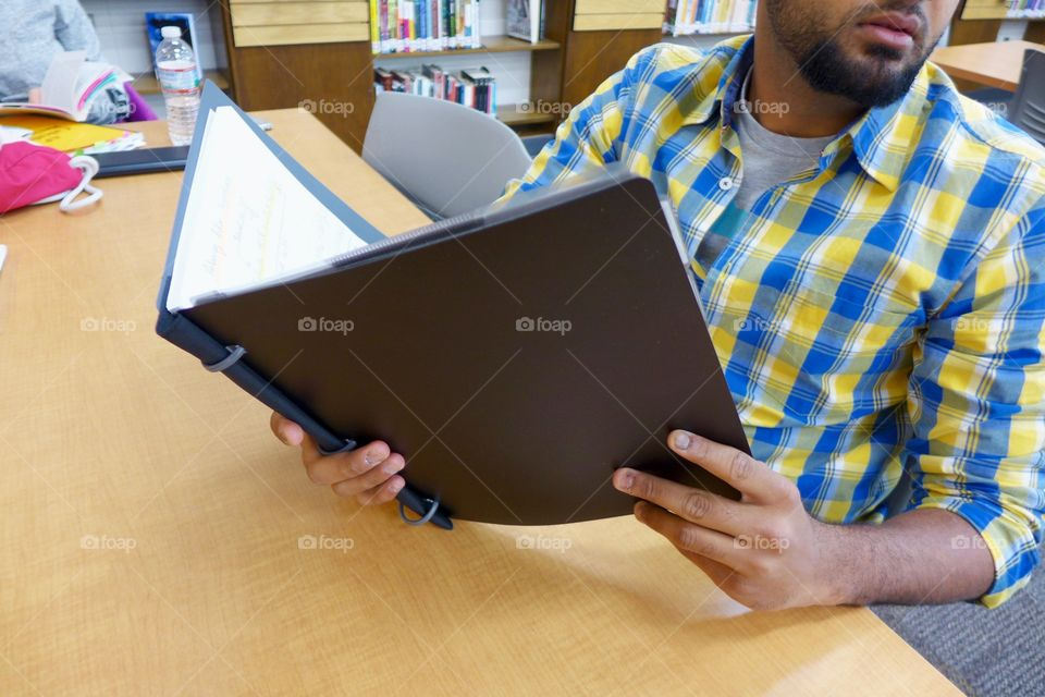 Young adult teenage male student holds notebook while studying in school library