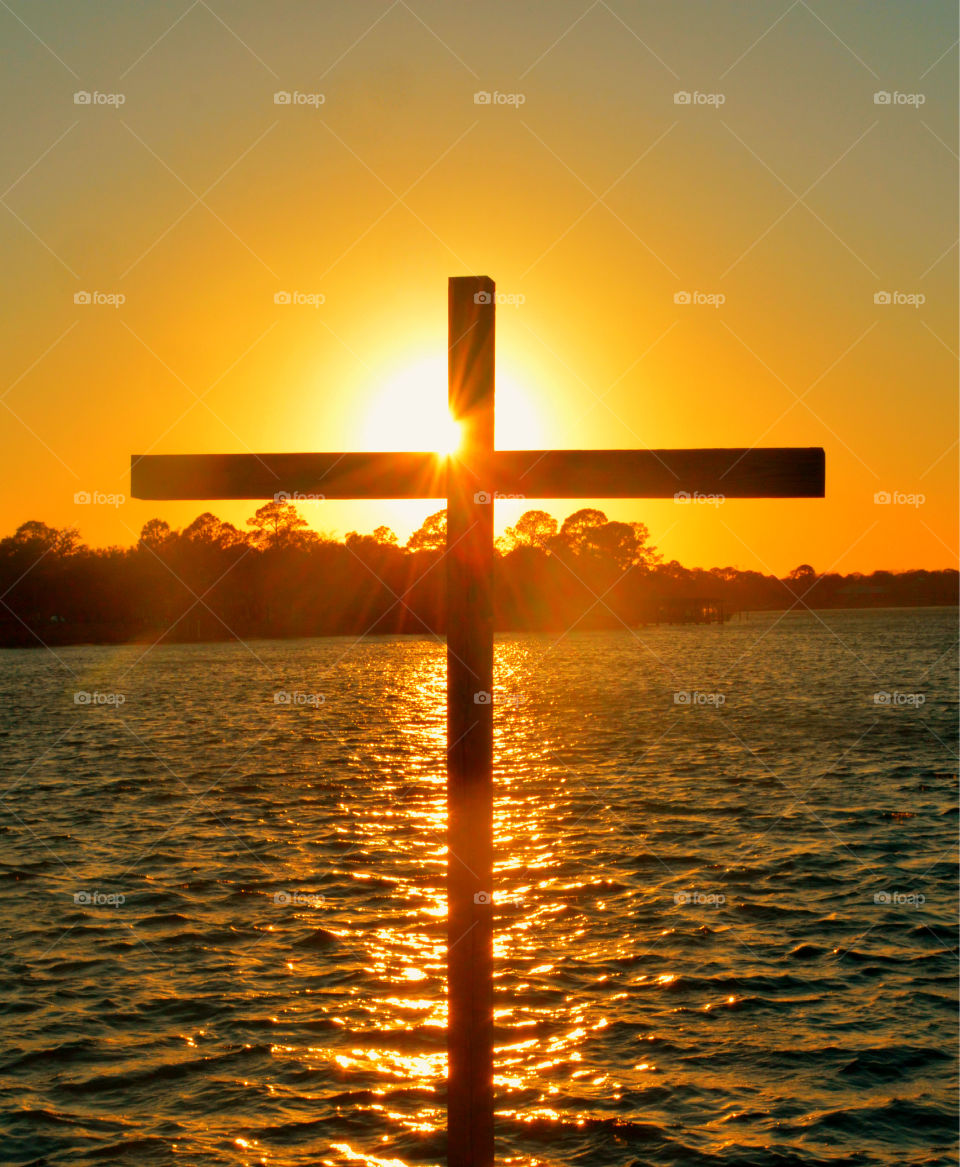 Silhouette of cross against lake at sunset
