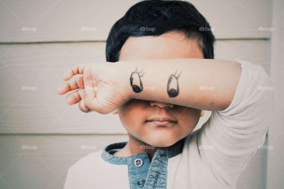 Close-up of a child with eyes drawn on his wrist
