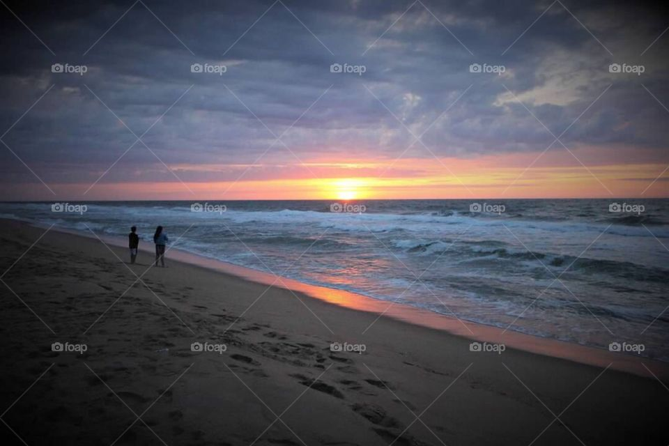 Young boy and girl standing along the sand watching the sun peak its way over the horizon.