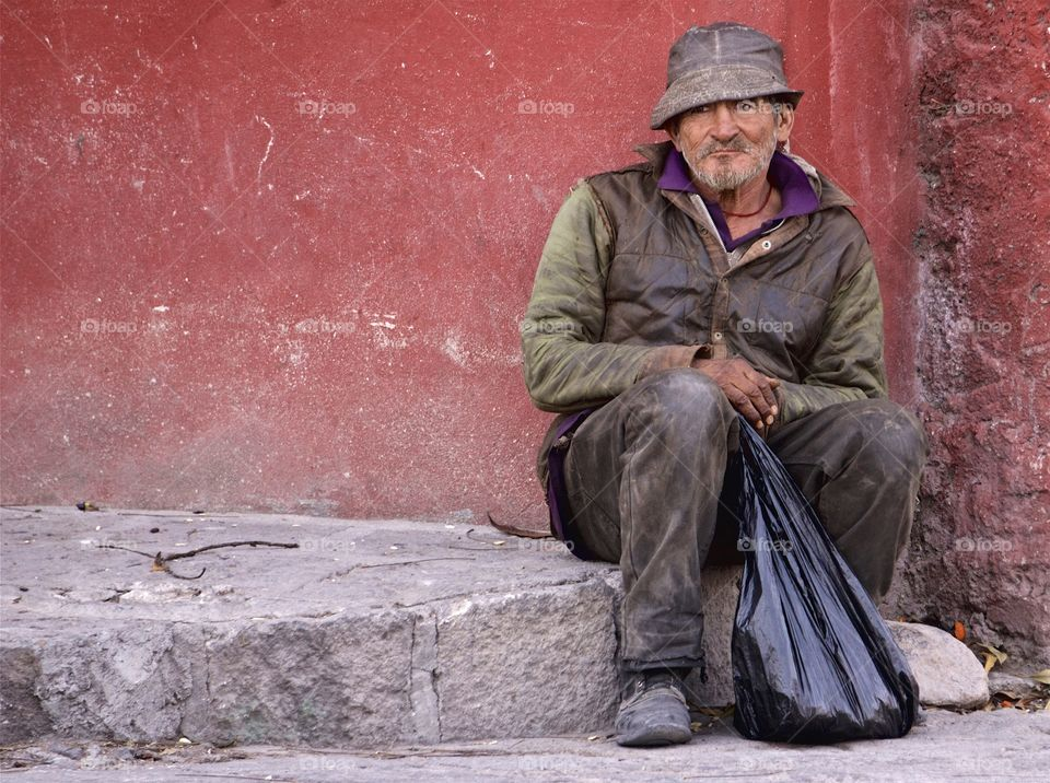 "A man is seated on the sidewalk near the Mercado San Juan de Dios"" in San Miguel de Allende, Mexico"