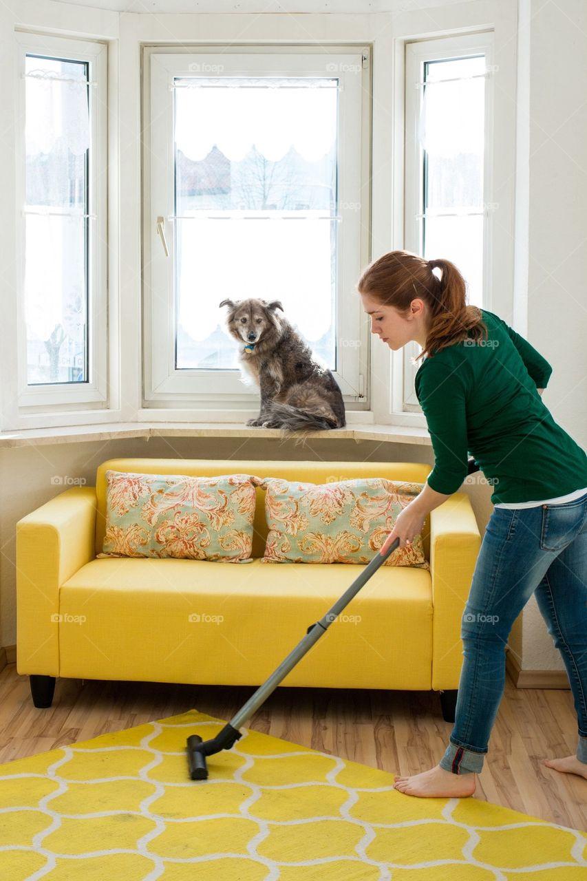 Woman vacuuming room with dog sitting near window