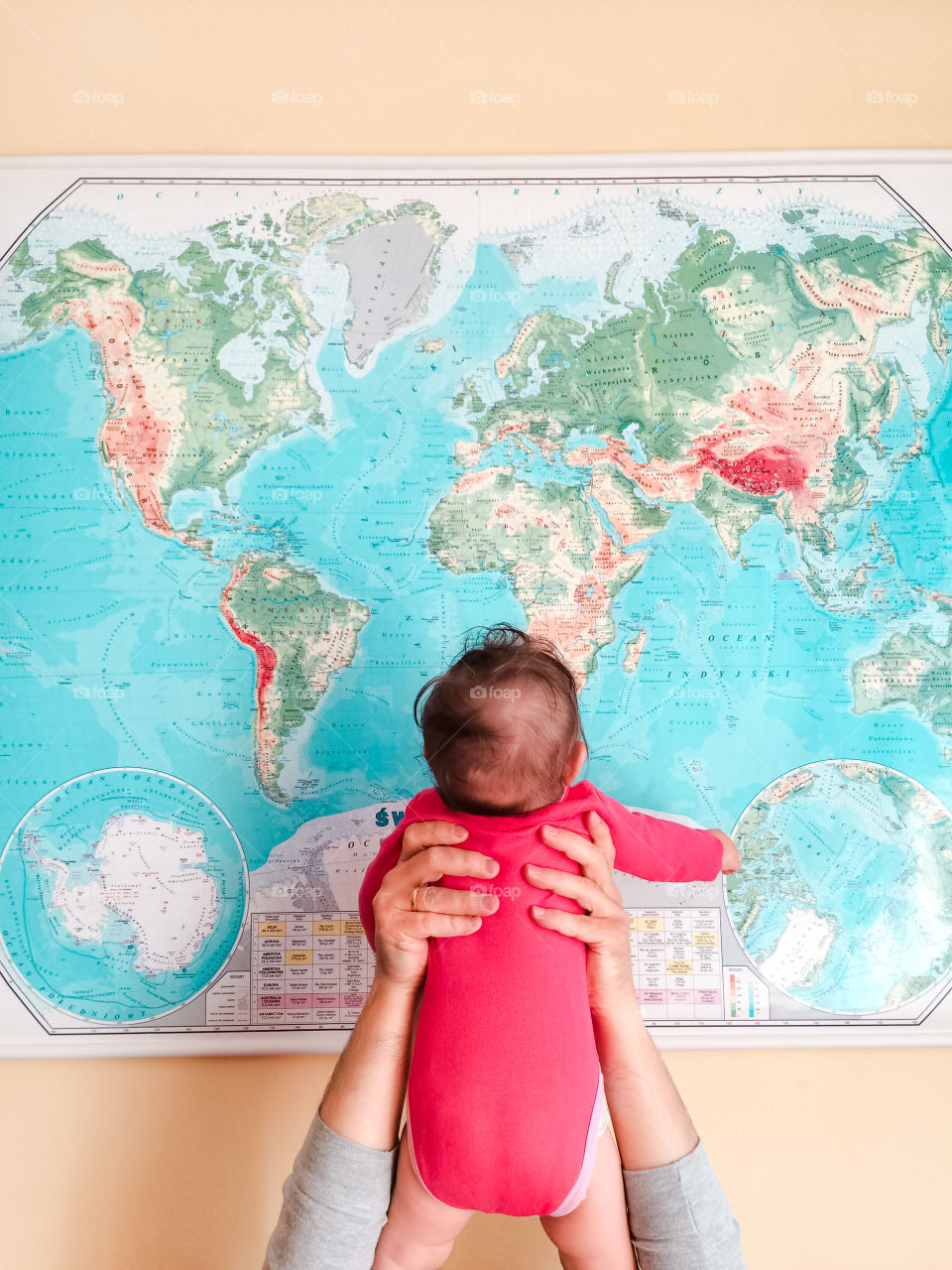 Mother hand holding little baby in front of map