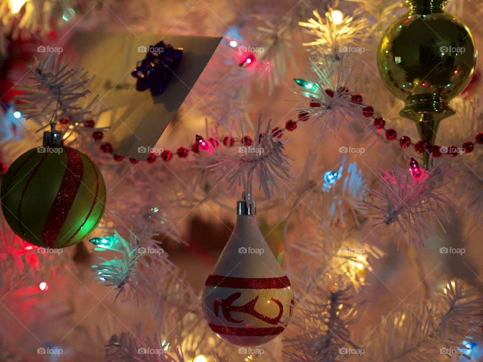 Ornaments hanging from a Christmas tree with a peaceful glow during the holiday season.