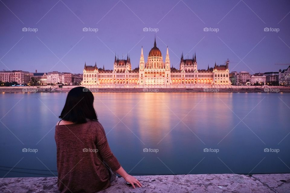 Girl sitting by the Danube River watching Hungarian Parliament Building