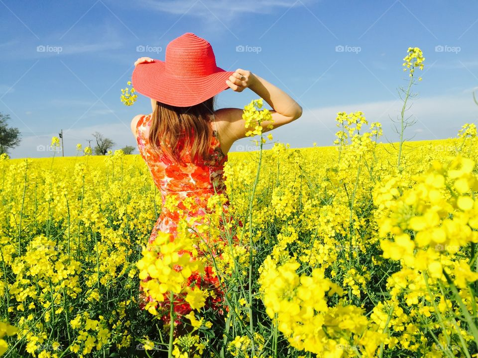 Rear view of a woman in rapeseed field