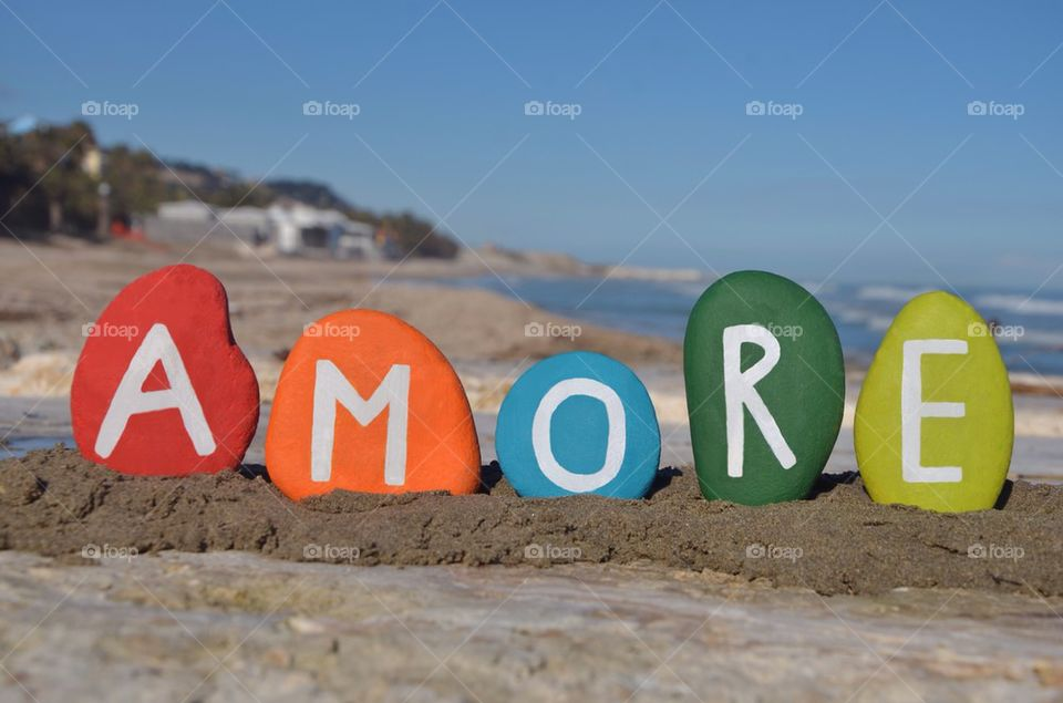 Amore, love in italian language on colourful stones