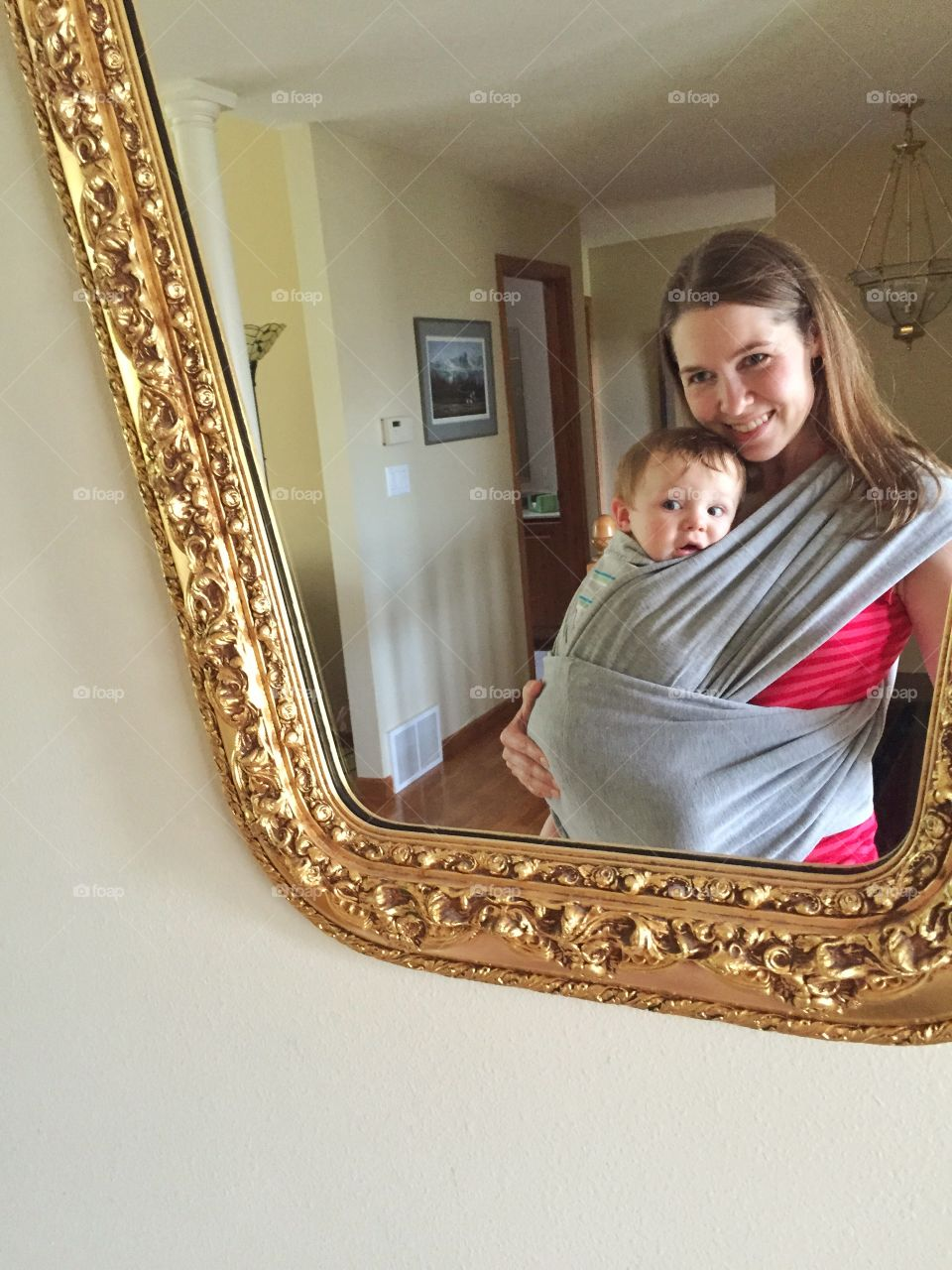 Reflection of mother carrying her cute baby boy in sling