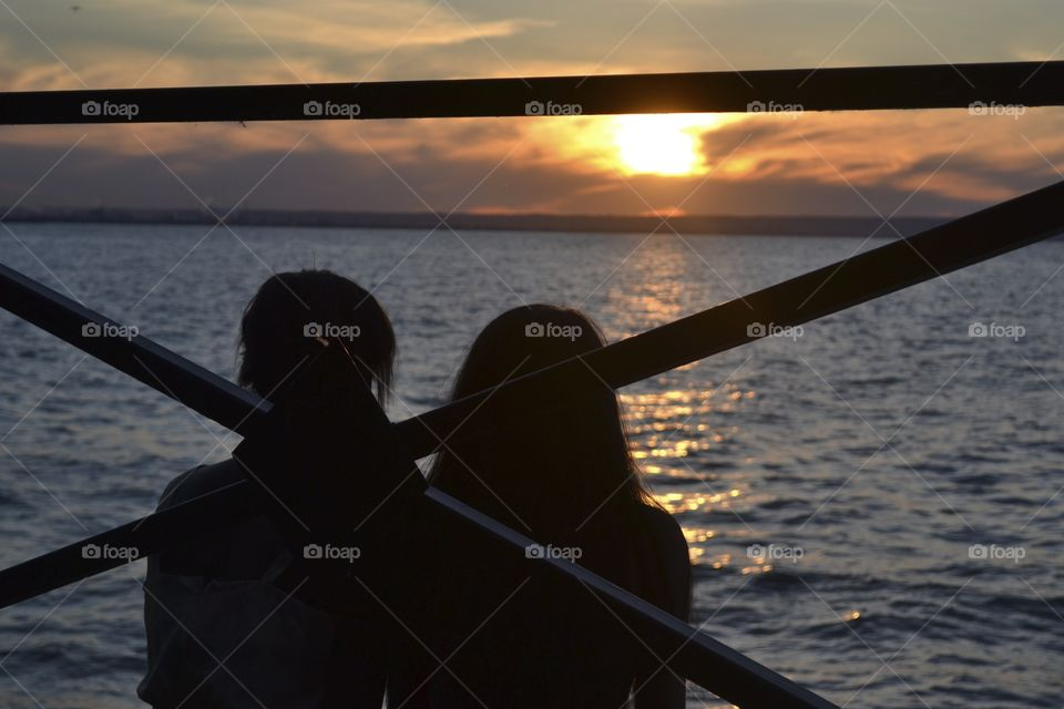 Couple watches the sunset over the lake.