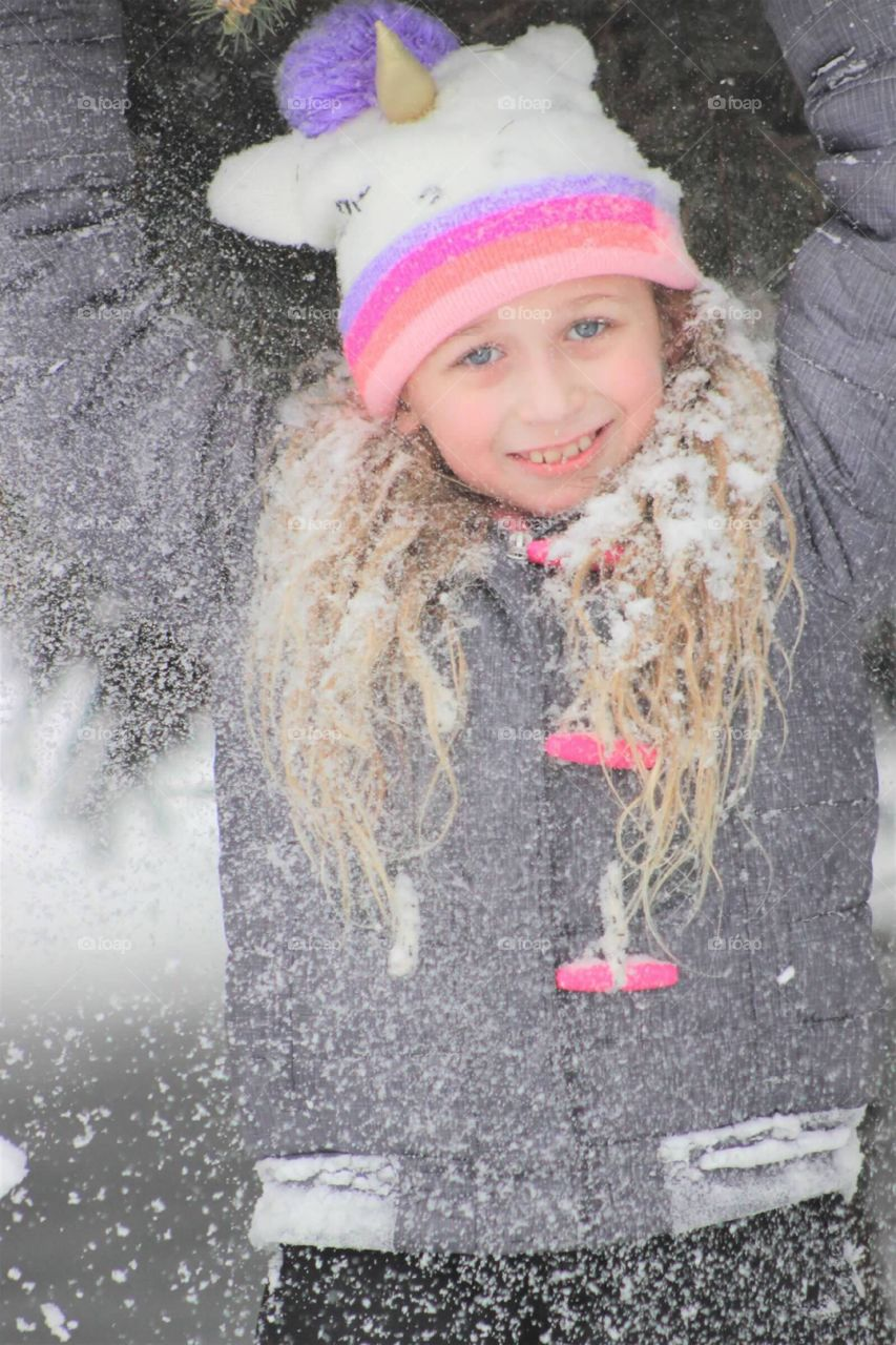 Playful little blue-eyed blonde haired girl covering herself in snow as she plays outdoors in winter.