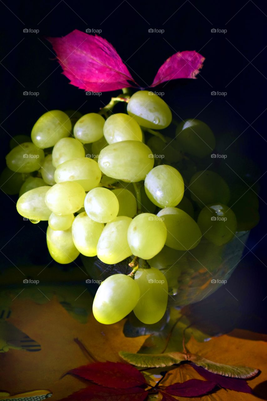 Autumn still life.Ripe grapes lie on a table in autumn dry leaves