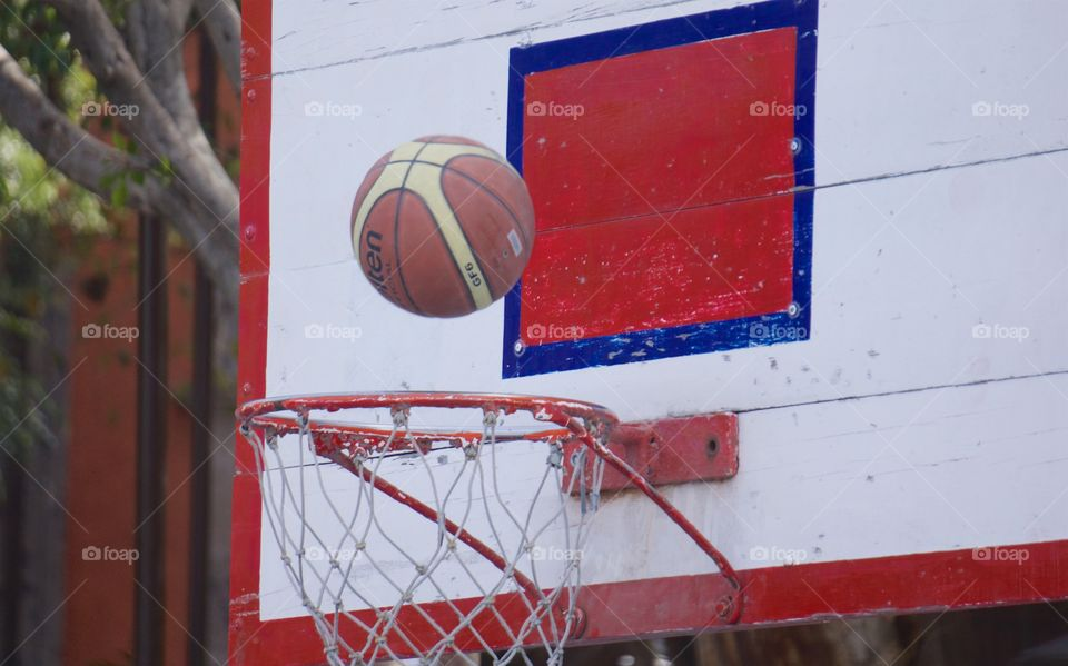 During a basketball game in San Miguel  de Allende, Mexico, the ball is about to go through the hoop for a basket,